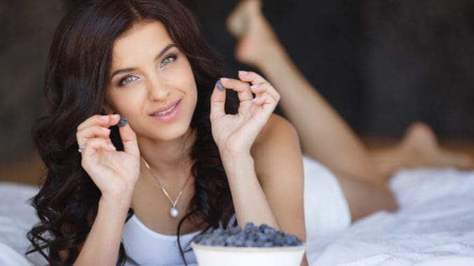 Beautiful young woman eating fresh summer blue berries and raspberry