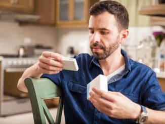Attractive man with a beard holding a couple of boxes of medicine and comparing each other at home