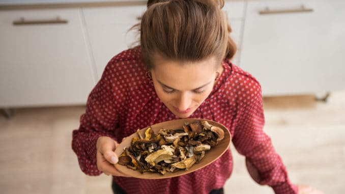 a woman is standing, breathing in the rich, earthy smell of dried mushrooms as she stands in a kitchen.