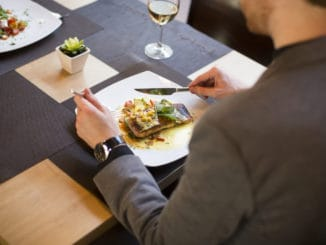 Young man eating grilled salmon with sauce and herbs served at restaurant