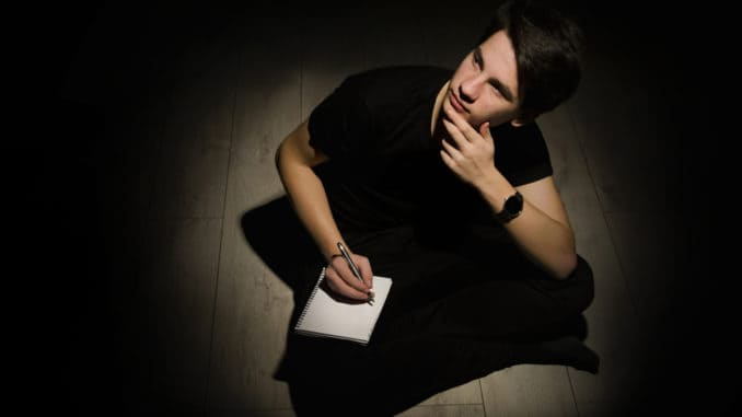 Teenager young man thinking and writing on notebook on black background