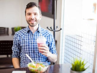Portrait of a young Latin man eating some healthy food and enjoying a smoothie alone at a restaurant