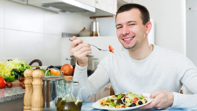 Happy adult guy having healthy lunch with the veggies at the home