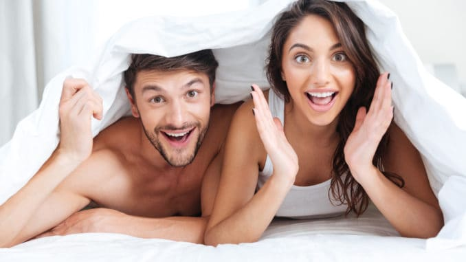 Happy smiling couple lying in bed covered with blanket at home