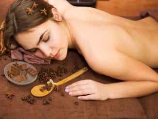 Beautiful woman in spa salon having chocolate therapy procedure with coffee seeds, cinnamon sticks, star anise