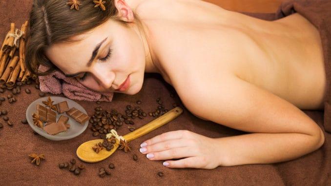 Beautiful woman in spa salon having chocolate therapy procedure with coffee seeds, cinnamon sticks, star anise