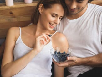 Man holding bowl of blueberries for his woman
