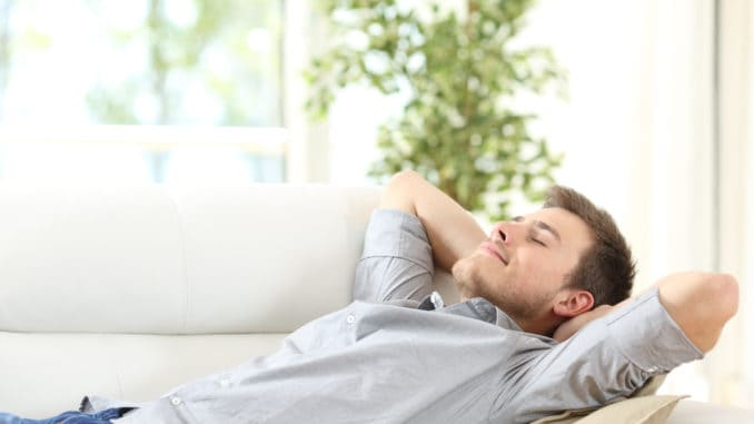 Relaxed man resting lying on a couch with the hands on the head at home