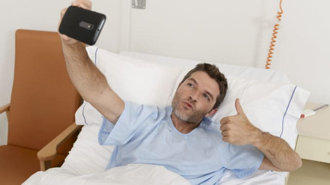 Young attractive man lying on bed hospital clinic holding mobile phone taking self portrait selfie photo giving thumb up in optimist recovery concept and health care positive image