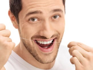 Man flossing his teeth isolated on white background
