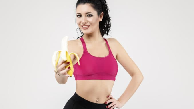 Attractive fit woman eating banana, isolated on Background.