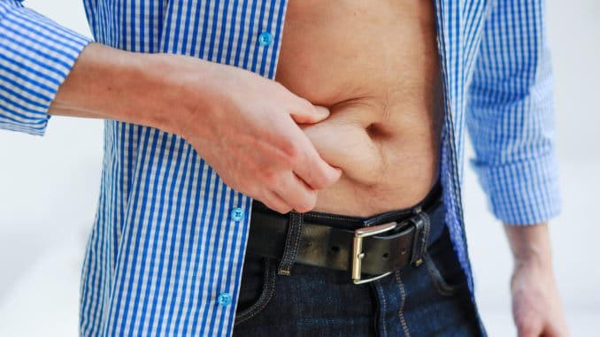man wearing a blue and white checkered shirt is pinching his belly fat with his right hand