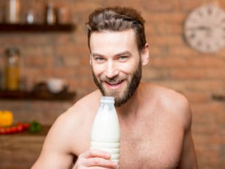 Muscular man drinking milk from the bottle on the kitchen