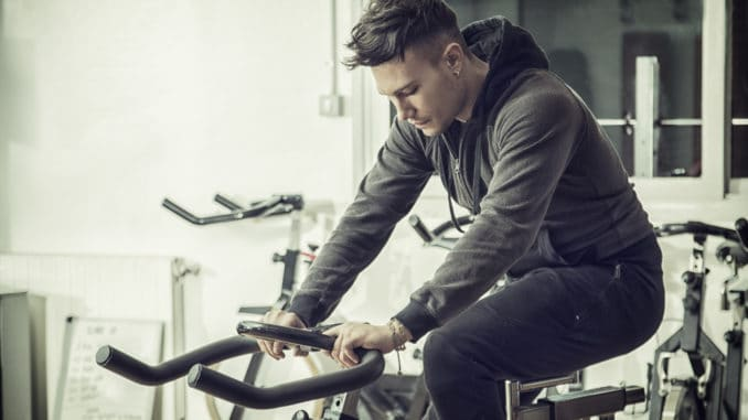 Attractive young man exercise in gym: spinning, exercising on stationary bike