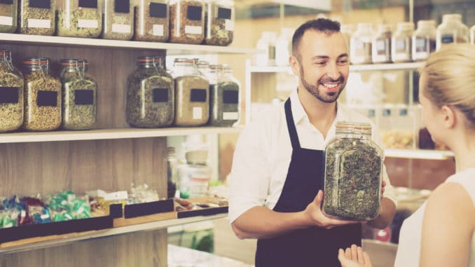 Man seller holding glass can with dried herbs in organic shop