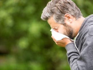 Man with allergy sneezing