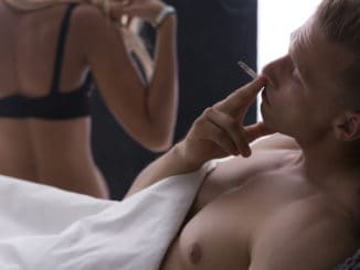 Young handsome men smoking cigarette in bed after sex