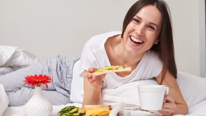 Mid shot of beautiful smiling girl eating sandwich with avocado and drinking aromatic tea