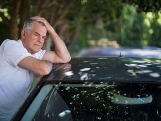Tensed senior man with head in hand leaning on car