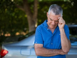 Tensed senior man standing by car against trees