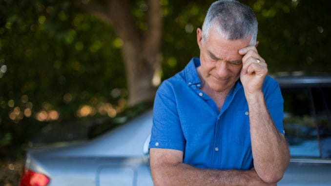 Tensed senior man standing by car against trees