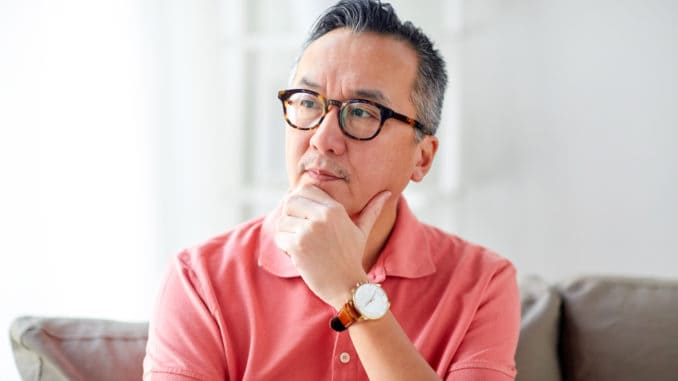 People concept - asian man thinking at home