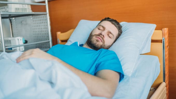 Young sick man sleeping on hospital bed at ward