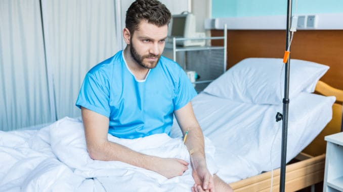 Sick bearded man sitting on hospital bed with drop counter