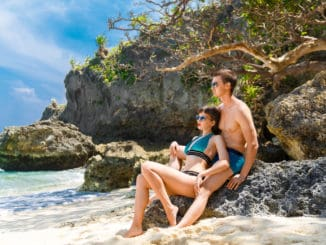 Young couple in bathing suits on rocks on a tropical island. Summer vacation concept.