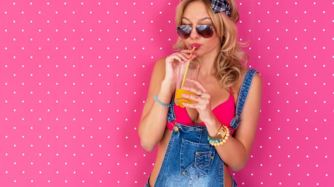Young woman drinking juice or cocktail in underwear bra Outdoors, lifestyle