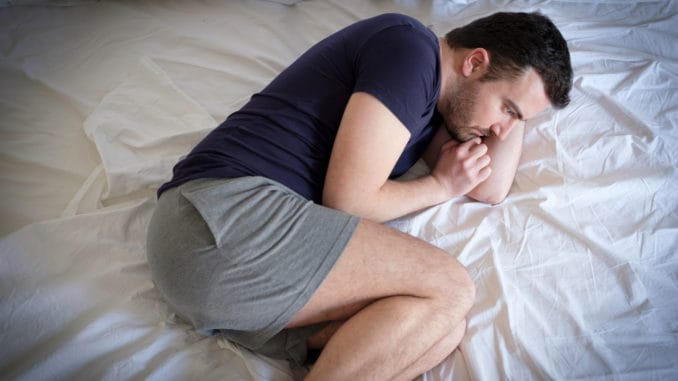 Sad and upset man trying to sleep in his bed