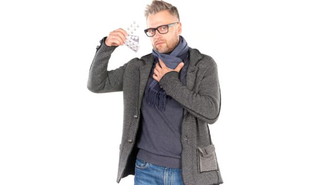 man wearing warm scarf and holding pills