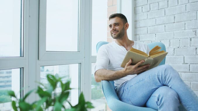 Young man reading book sitting on balcony in modern apartment