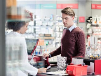 Portrait of a handsome young men smiling while buying an useful pharmaceutical product in a modern drugstore with various medicines and helpful personnel