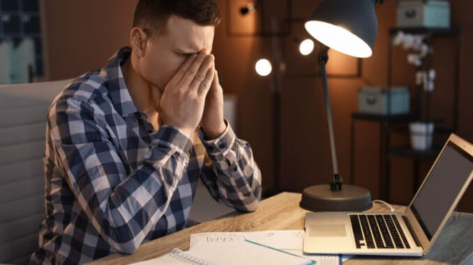 Overworked man with headache in office