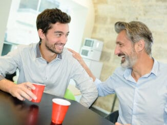 Men laughing and drinking coffee me