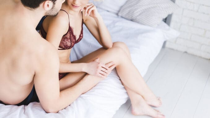 cropped shot of young couple looking at each other in foreplay on bed