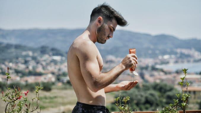 Shirtless Young Man Putting on Sunscreen Cream