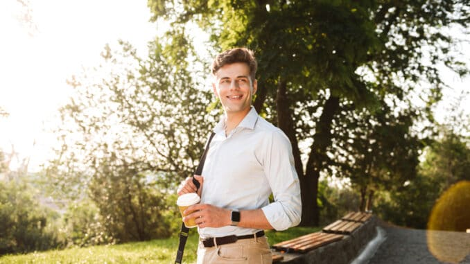 Happy young man in shirt walking at the city park with cup of coffee