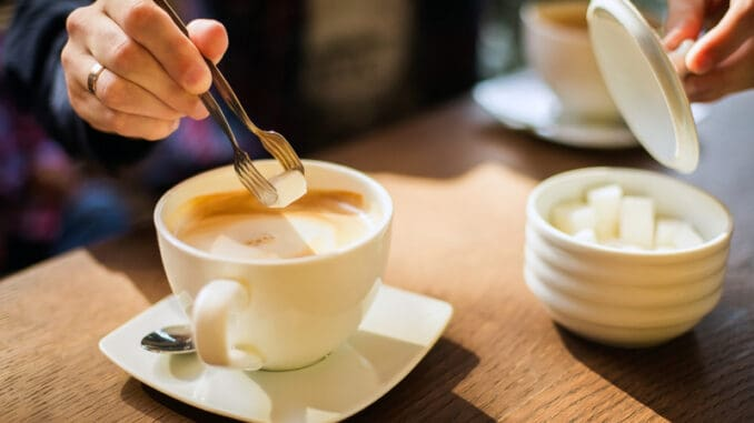 Man`s hand adding cube of white sugar to his coffee or cuppuchino