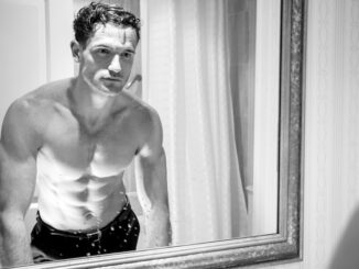 Attractive shirtless man with muscular body and sixpack abs looking at his reflection in bathroom mirror