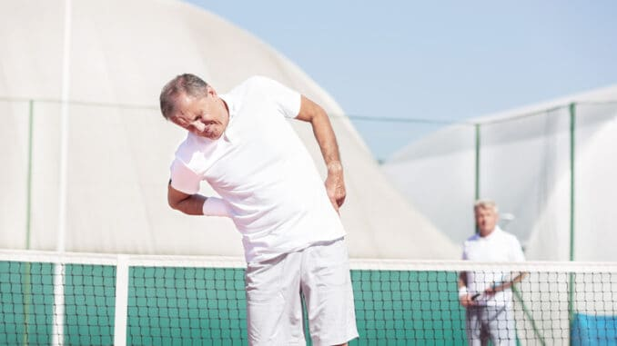 Senior men with backache while standing against friend during tennis match on sunny day