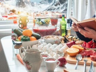 Man reading book with preparing food on dining table with snowing on village in wintertime