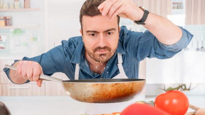 Cheerful young man preparing food at home