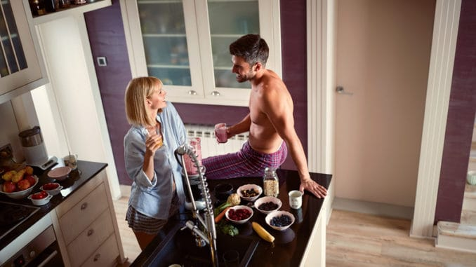 Woman and men in love in the kitchen drinking smoothie and juice