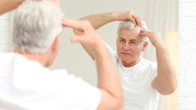 Senior man with hair loss problem looking in mirror indoors