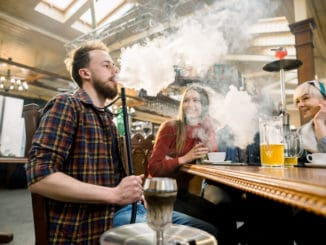 Close-up shot of a stylish bearded adult guy smoking hookah indoor of a cafe