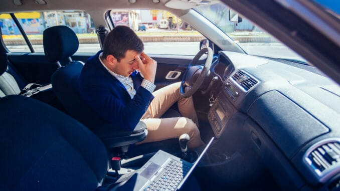 Reckless businessman driving in the city during the rush hour while typing on his laptop