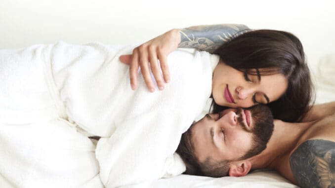 couple in love smiling while lying on bed together
