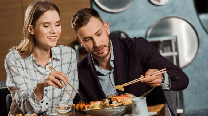 Happy young adult couple eating sushi rolls in restaurant